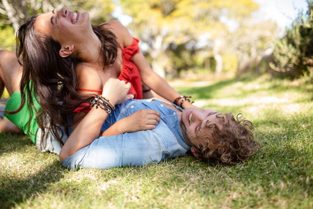 Romantic couple embracing while relaxing in park