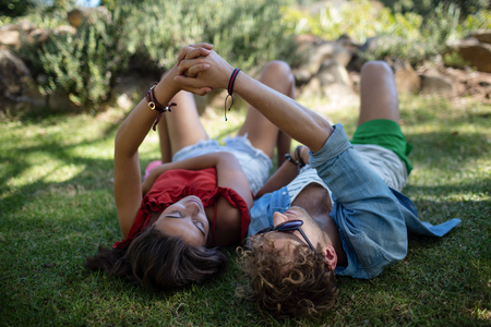 Couple holding hands while relaxing in park