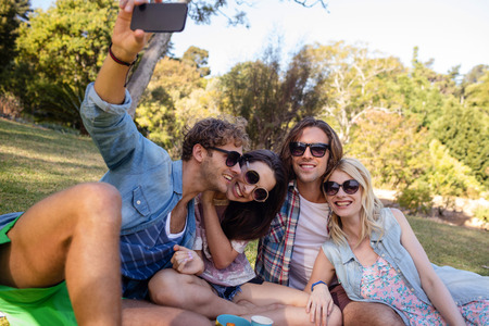 Friends clicking selfie while having picnic in park on a sunny day