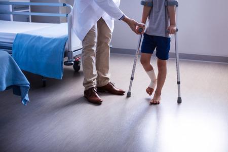 의사가 병원에서 목발로 걷기 위해 부상당한 소년을 돕기 스톡 콘텐츠