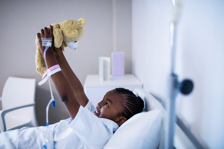 Patient playing with teddy while resting on the bed at hospital Stock Photo
