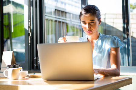 Focused female executive working on laptop in caf� Stock Photo