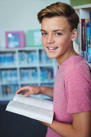 secondary school students: Portrait of happy schoolboy holding book in library at school