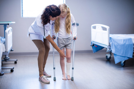 Female doctor assisting girl to walk with crutches in ward of hospital Stock Photo - 72894594