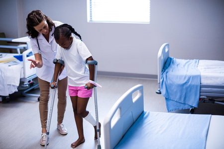 Female doctor assisting girl to walk with crutches in ward of hospital Stock Photo - 72894599