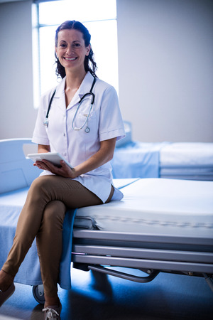 Portrait of female doctor using digital tablet in ward of hospital Stock Photo