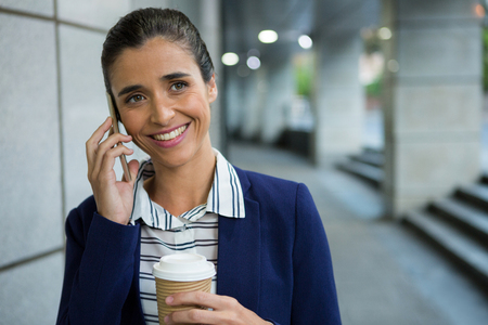 Smiling business executive talking on mobile phone while having coffee