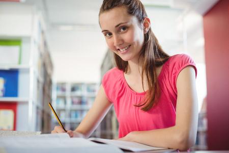 Portrait of smiling schoolgirl doing homework in in library at school