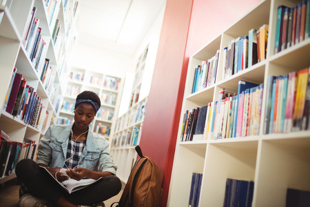 Schoolgirl listening music on headphones in library at school Stock Photo