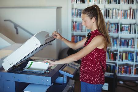 xerox: Attentive schoolgirl using Xerox photocopier in library at school