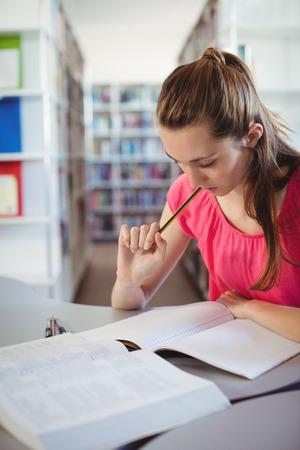 Attentive schoolgirl doing homework in in library at school