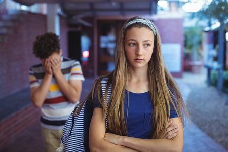 Upset school couple ignoring each other in school campus