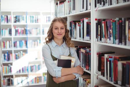 Retrato de colegiala feliz celebración de libros en la biblioteca en la escuela