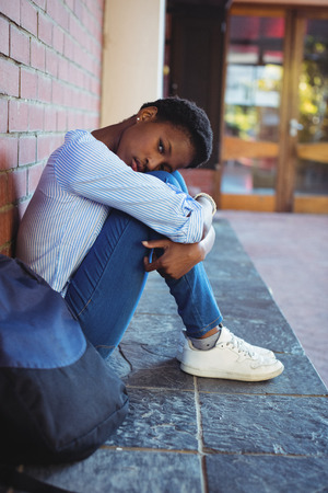 Portrait of sad schoolgirl sitting against brick wall in school campus