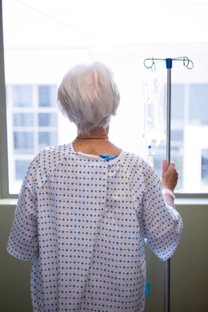 Rear-view of thoughtful senior patient standing at hospital