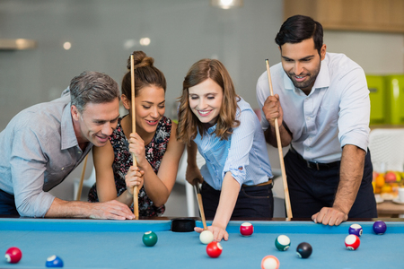 Smiling business colleagues playing pool in office space Banco de Imagens - 72895876