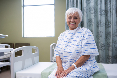 Portrait of smiling senior patient sitting on bed in hospital Stock Photo