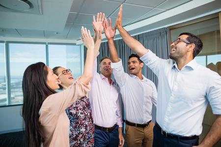 オフィスで会議中にハイファイブを与える笑顔ビジネス部門の同僚 写真素材