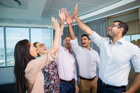 Smiling business colleagues giving high five during meeting in office 스톡 콘텐츠
