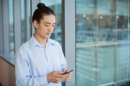 Business executive using on mobile phone in corridor at office