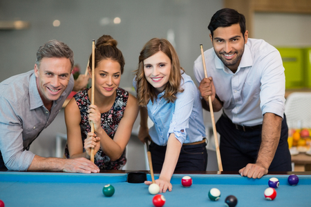 Portrait of smiling business colleagues playing pool in office space