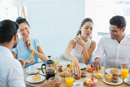 Business colleagues interacting with each other while having breakfast in office cafeteria Stock Photo