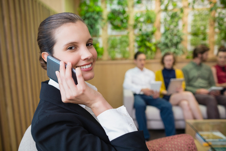 Portrait of beautiful business executive talking on her mobile phone while sitting in office lobby