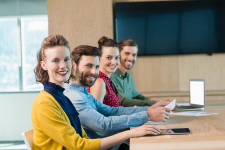 Portrait of smiling business executives sitting together in conference room at office