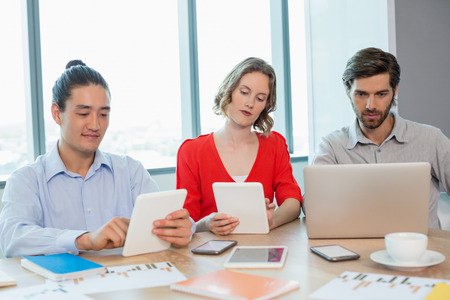Business executives using laptop and digital tablet in conference room at office