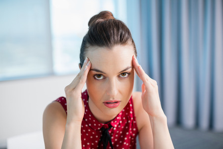 Portrait of tense female business executive sitting with hand on forehead in office