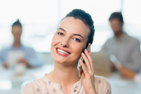 Portrait of beautiful business executive talking on her mobile phone in conference room Stock Photo