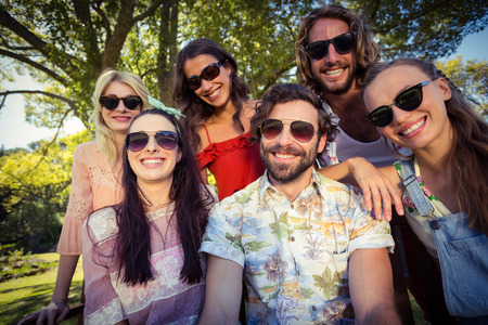 Group of friends smiling in park on a sunny day