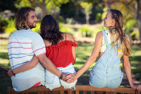 Rear view of man cheating on her woman in park Stock Photo