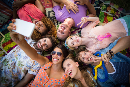 Group of friends lying in a circle and taking selfie on a sunny day