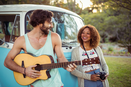 Man playing guitar near campervan while woman standing beside him on a sunny day Stock Photo