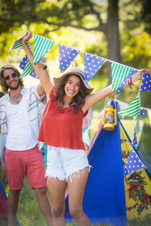 Woman holding bunting at campsite on a sunny day Stock Photo