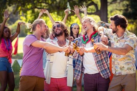 Happy friends toasting beer bottles at campsite on a sunny day Stock Photo