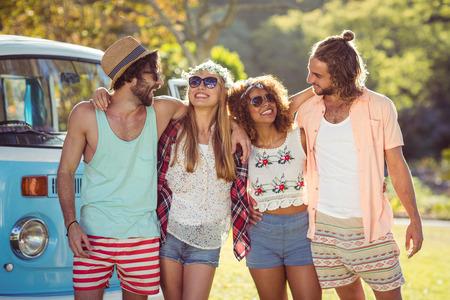 Des amis souriants debout ensemble dans un parc en journée ensoleillée photo