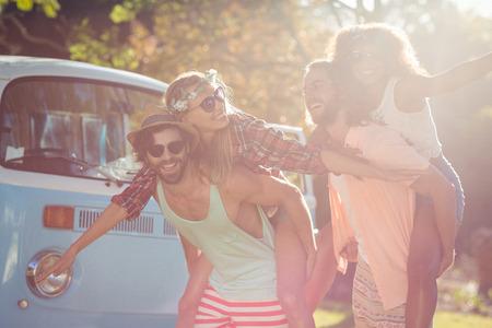 Zwei glückliche Paare mit piggy Fahrt im Park an einem sonnigen Tag Standard-Bild - 73436153