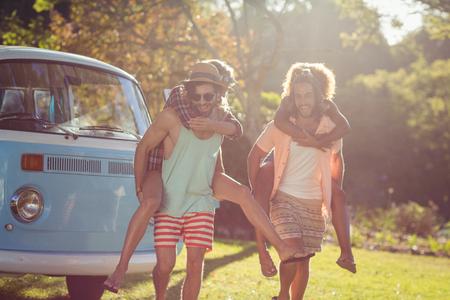 Deux couples heureux ayant une promenade dans le parc en journée ensoleillée photo