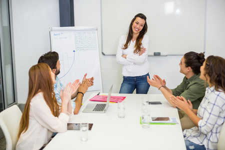 Executives appreciating their colleague during presentation in conference room at office