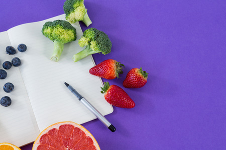 Measuring tape, various fruits, vegetable, opened book and pen on purple background
