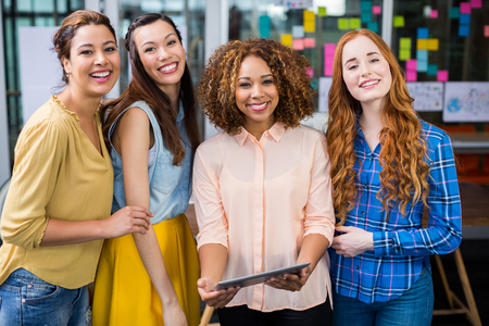 Portrait of smiling female executives discussing over digital tablet in office
