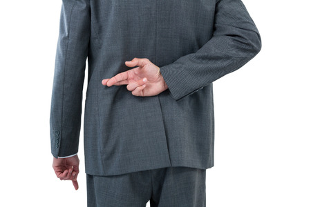 deceptive: Businessman standing with figure crossed against white background