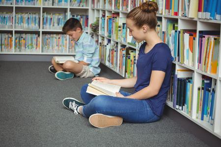 Pozorné školní děti čte knihy v knihovně ve škole