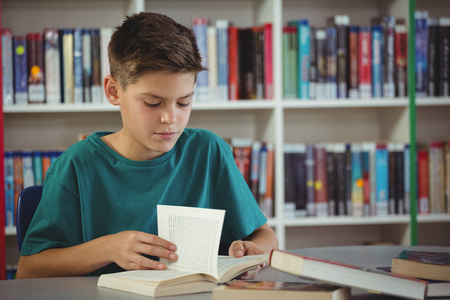 turning the page: Attentive schoolboy reading book in library at school