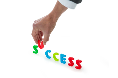 Hand of businessman arranging success word against white background Stock Photo