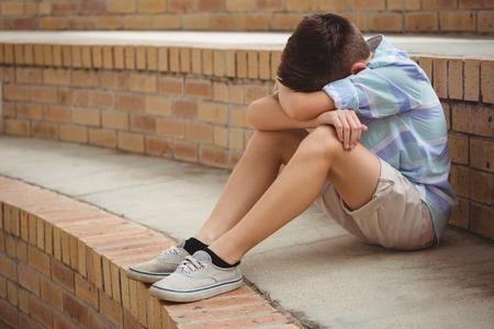 Triste colegial sentado solo en los pasos en el campus de la escuela