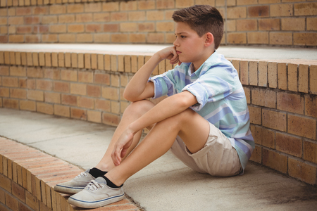 Sad schoolboy sitting alone on steps in campus at school Stock Photo