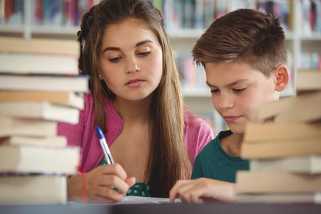 Pozorné školní děti dělají domácí úkoly v knihovně ve škole